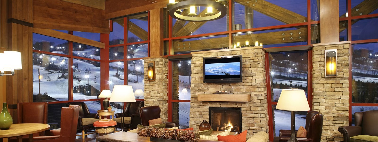 Interior lodge with fireplace and ski resort in background