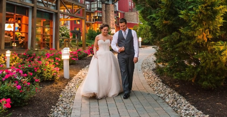 Newlyweds walking along path in front of wedding venue in pennsylvania