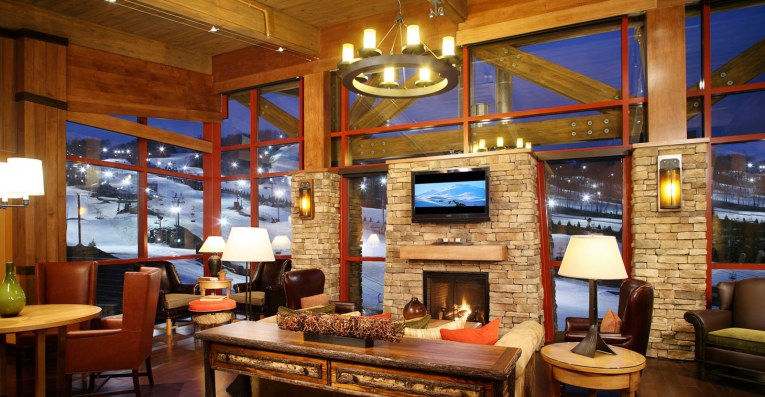 large hotel entry space with fireplace against backdrop of ski hill