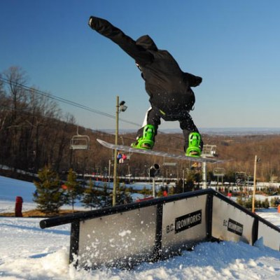 snowboarder jumping on rail