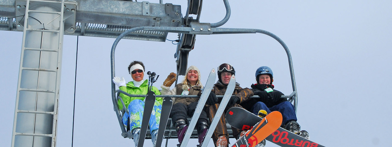 skiers and snowboarder family on chair lift