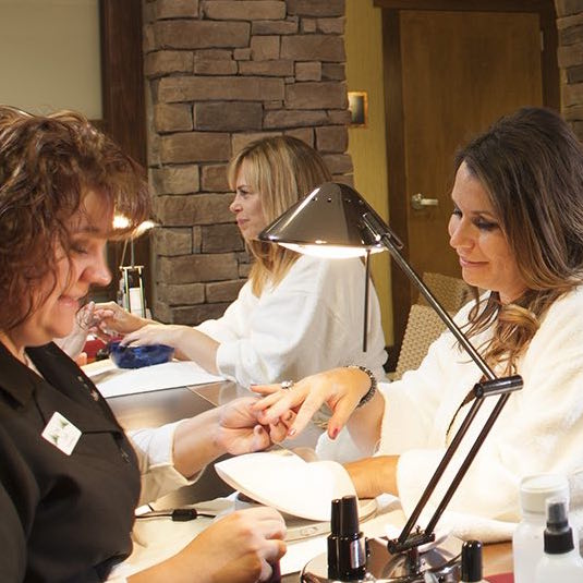 Two women receiving nail treatments